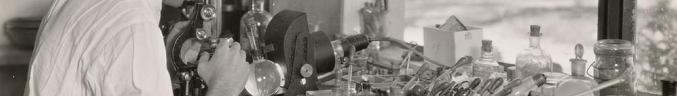 Black and white photo of man operating microscope on lab desk